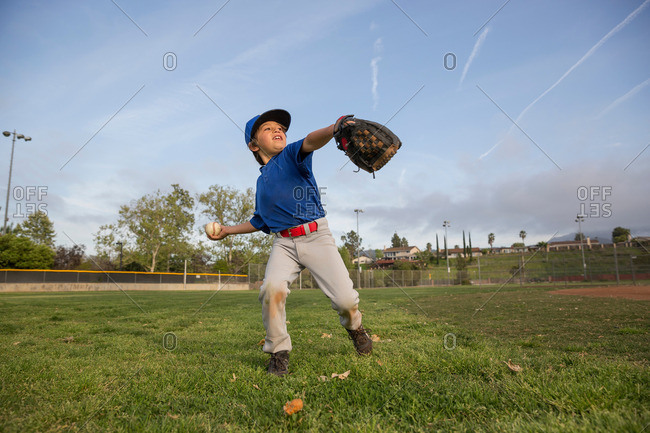 Boy throwing ball at practice on baseball field