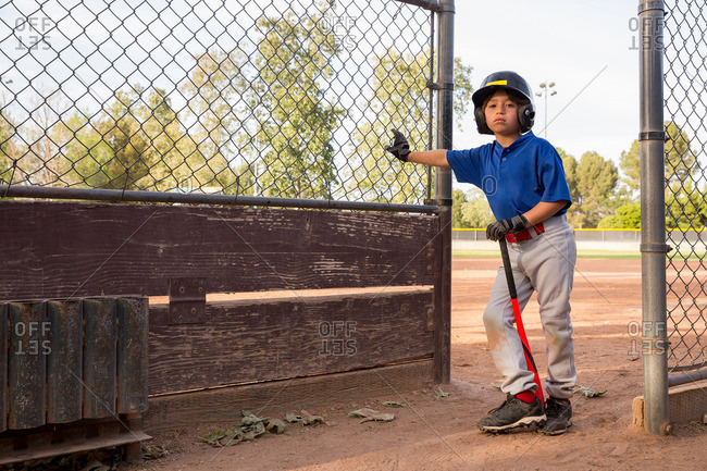 Portrait of boy with baseball bat leaning against fence at baseball practice