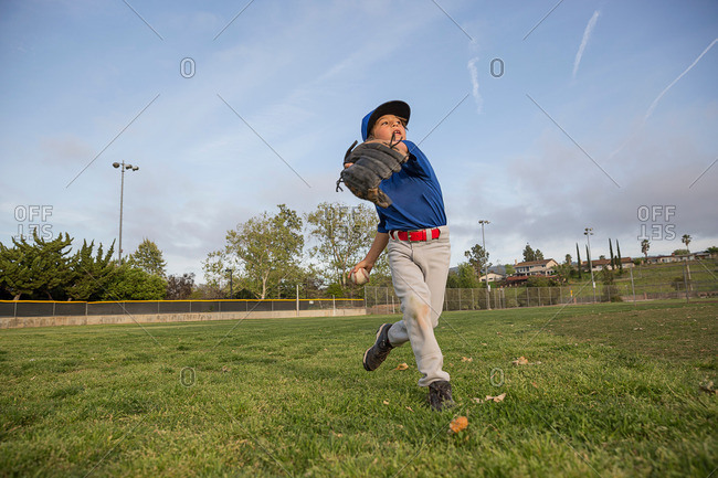 Boy throwing ball during practice on baseball field