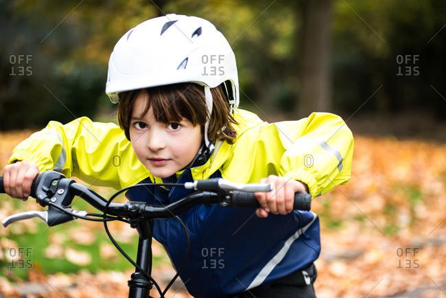 Boy wearing bicycle helmet on bicycle looking