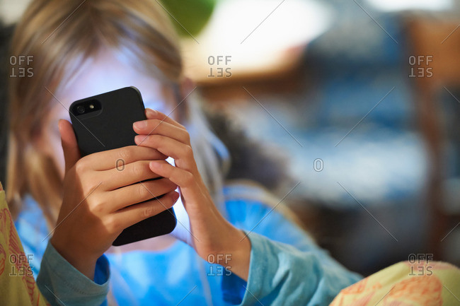 Young girl looking at smartphone, face illuminated by glow of screen
