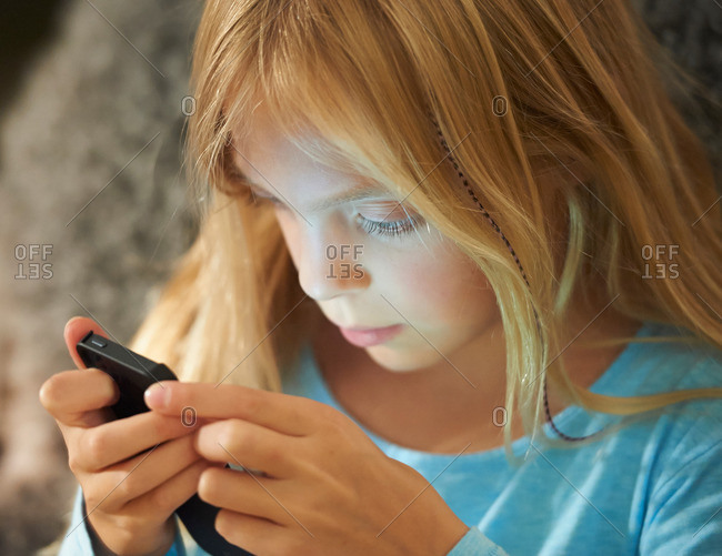 Girl looking at smartphone, face illuminated by glow of screen
