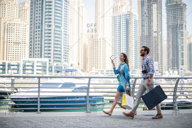 Couple strolling on waterfront carrying shopping bags