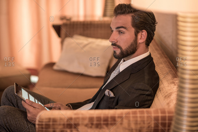 Young businessman sitting on hotel sofa using digital tablet
