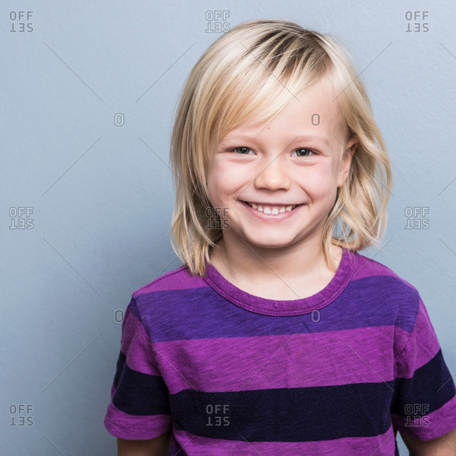 Portrait of blonde haired boy looking ahead smiling