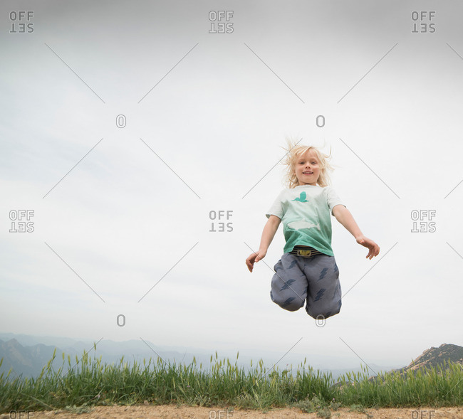 Boy jumping in mid air looking ahead smiling