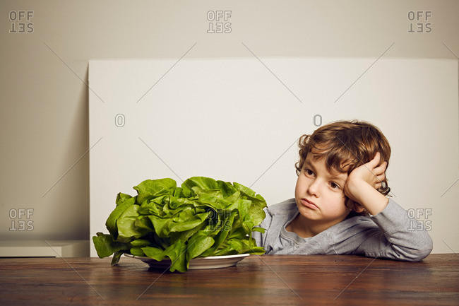 Boy sitting at table with plate of lettuce looking disappointed