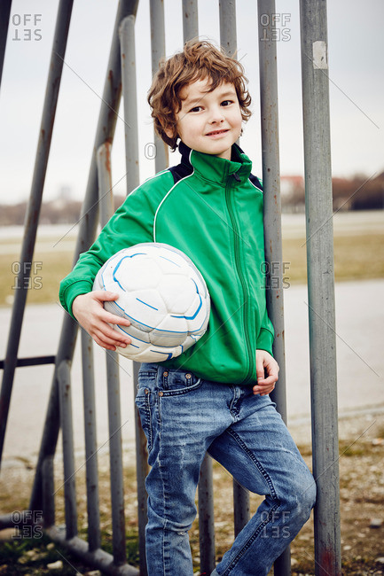 Boy leaning against railings holding football looking ahead smiling