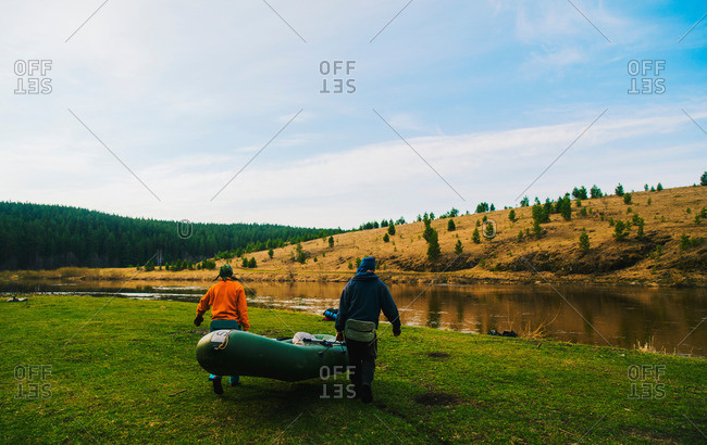 Rear view of couple carrying dinghy to river