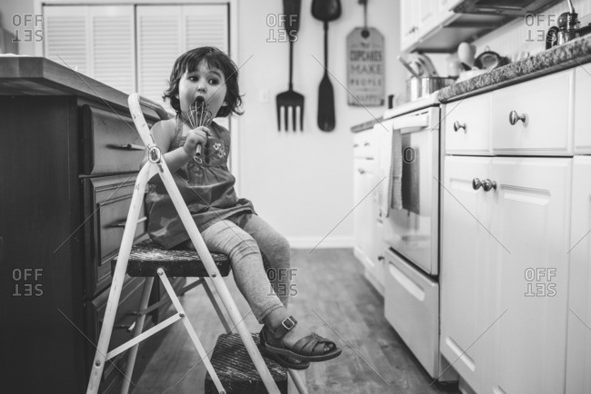 Little girl sitting in a kitchen licking a wire whisk