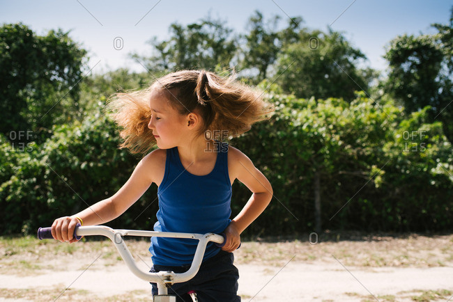 Little girl on a bicycle shaking her hair