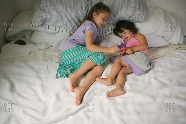 Sisters lying together on a bed playing with a toy