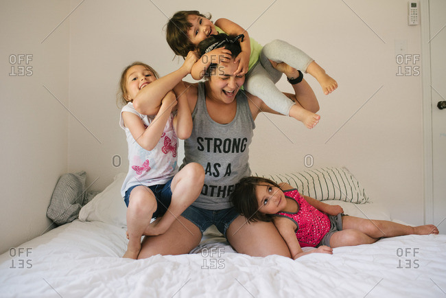 Mom wrestling with her three daughters on a bed