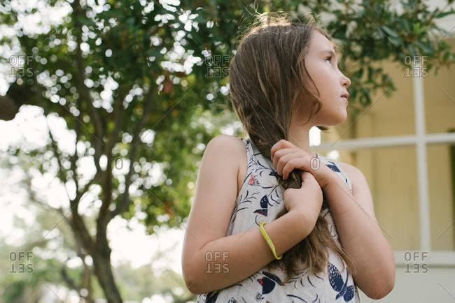 Little girl standing outside holding her hair