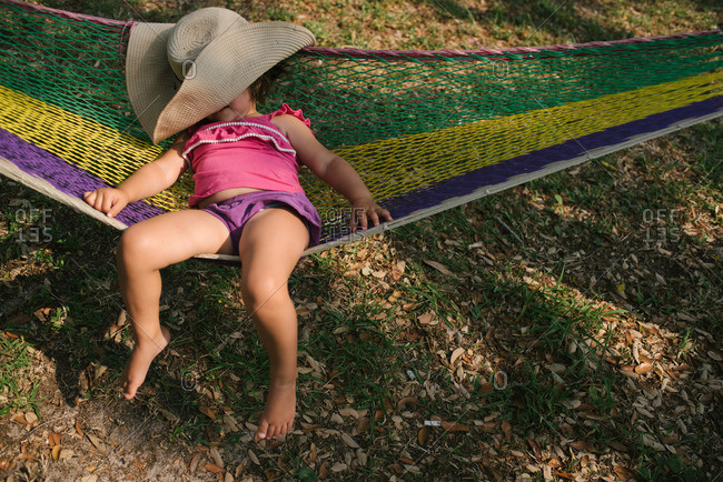 Little girl sleeping with a hat over her face in a hammock