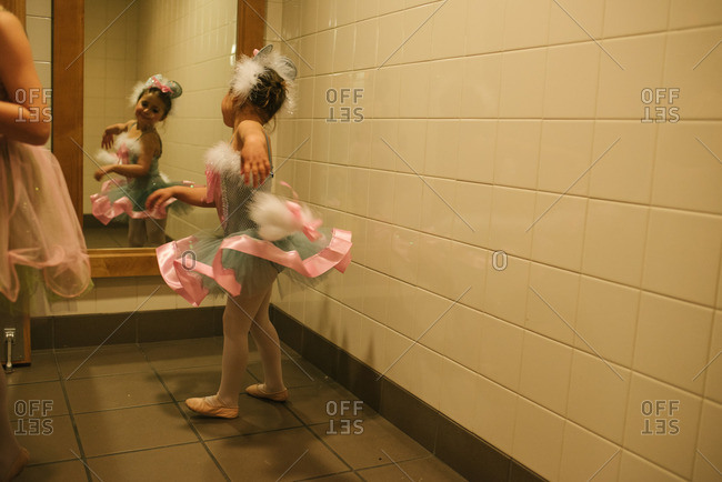 Little girl wearing a tutu looking at herself in a mirror