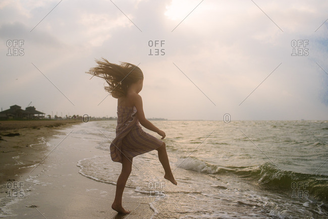 Girl wrapped in a towel skipping in waves on a beach