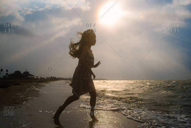 Girl wrapped in a towel running through waves on a beach