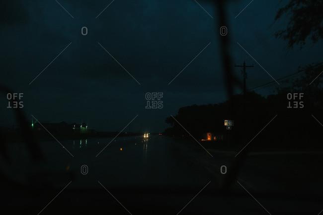 Highway on a rainy night through a windshield