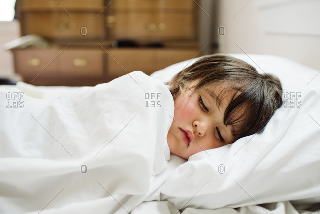Little girl curled up asleep in white sheets