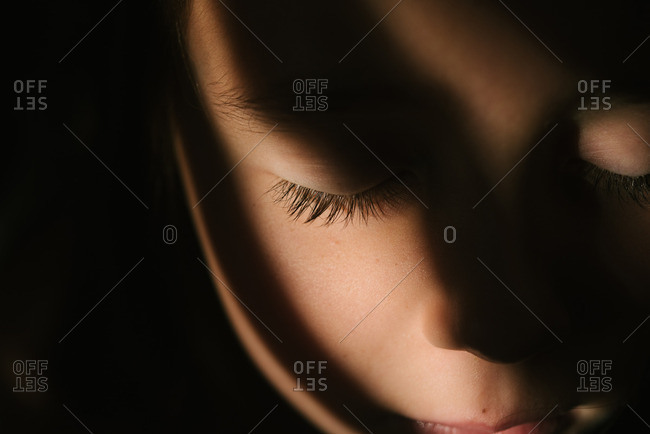 Girl with closed eyes in shadow