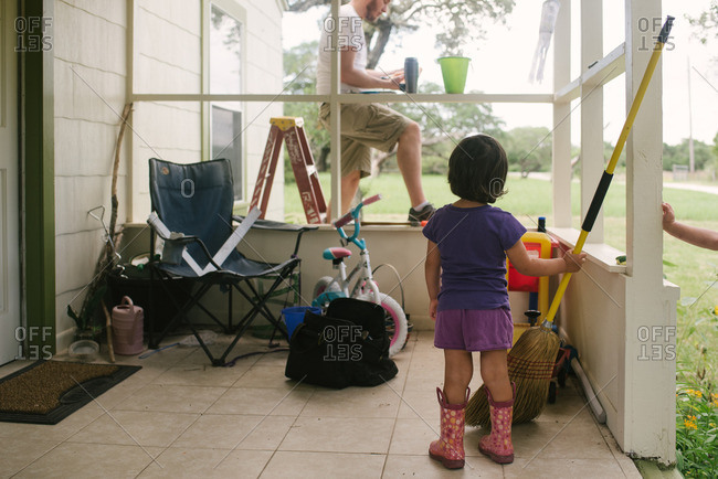 Little girl standing on a porch holding a broom while watching her dad