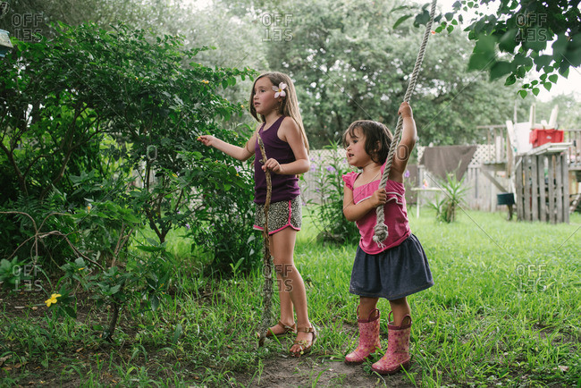 Sisters standing in a backyard playing with a stick and rope swing