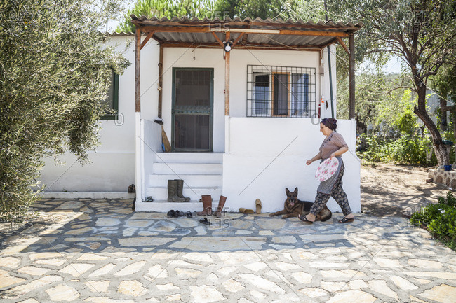 Dikili, Turkey - August 18, 2015: A woman walks past her dog on her way into her olive plantation farmhouse outside Dikili, Turkey