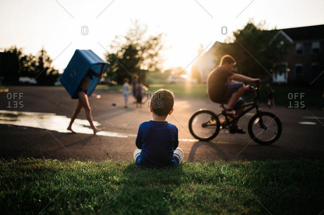 Boy watching kids in street