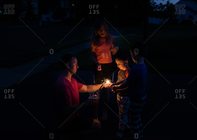 Man lighting sparkler for kids