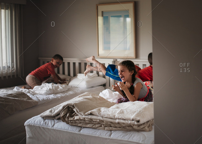 Three kids playing on beds