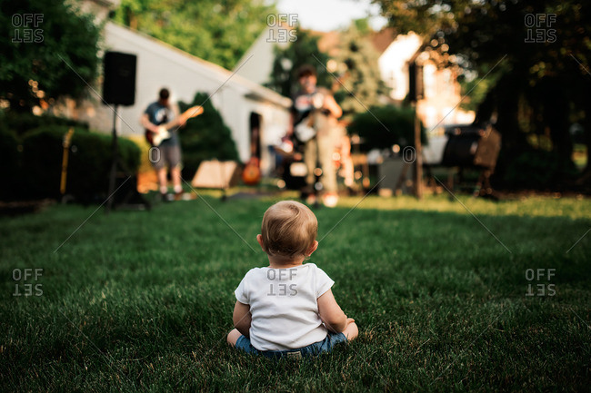 Toddler watching band play in yard