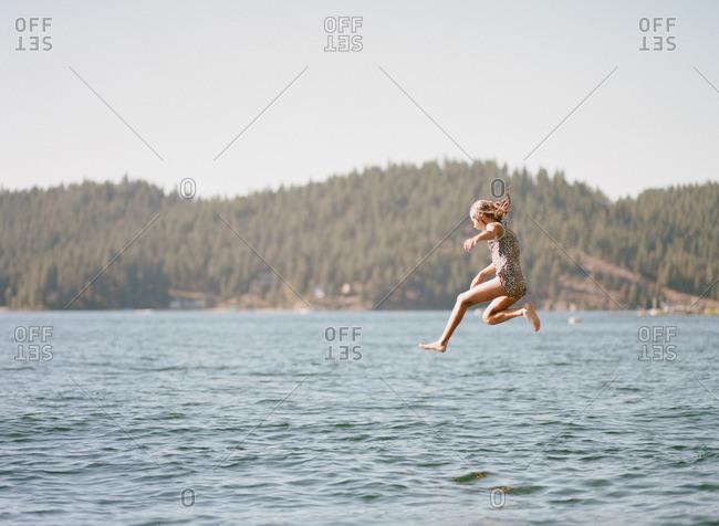 Girl jumping into a lake