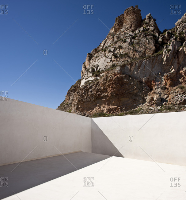 Balcony exterior of mountain house by Fran Silvestre set in rocks of Aroya, Valencia, Spain. Minimalist white design