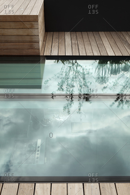 Glass floor in decked roof surface with reflection of plants in large planters and view down to kitchen, Notting Hill, London
