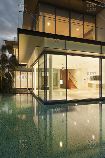View into lit house with reflections in water of residential house on Sentosa island, Singapore, South East Asia
