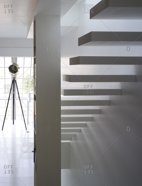 White cantilevered stairs and set light in hallway