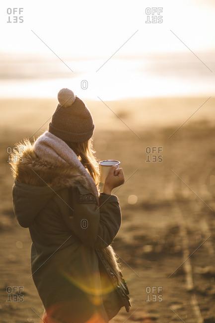 Woman in coat holding mug