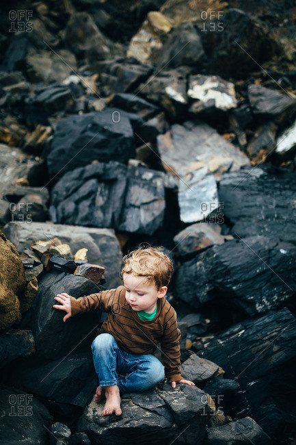 Boy climbing down rocky terrain