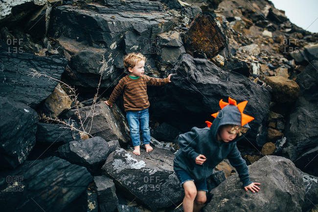 Brothers climbing on rocks