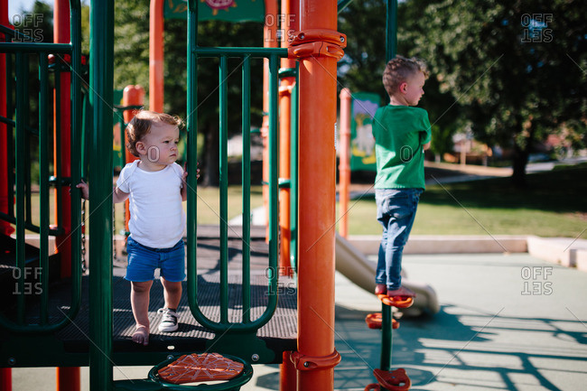 Children look out from a play structure at the park