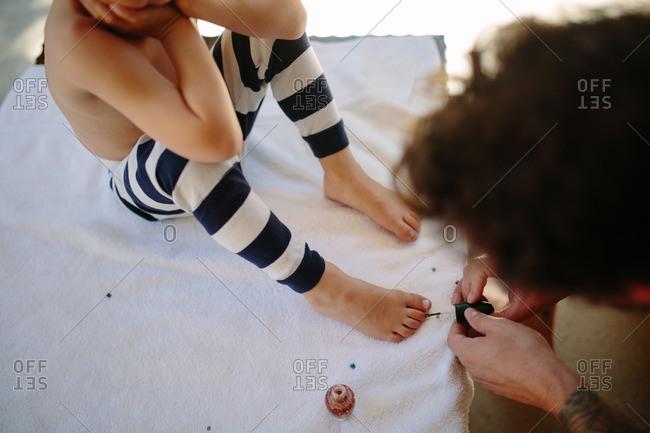 Father paints his child's toenails