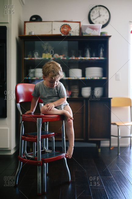 Boy sitting on chair looking down