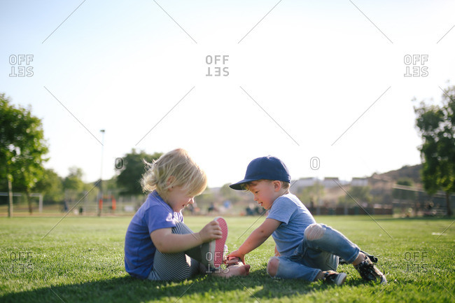 Girl removing shoes sitting next to boy