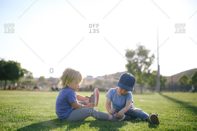 Two toddlers sitting on grass removing shoes