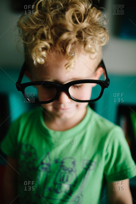 Child wears over-sized dark frame glasses