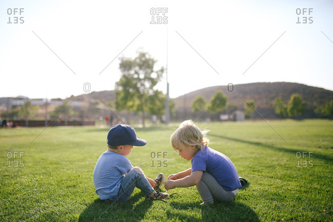 Boy sitting on grass removing shoes with girl squatting next to him
