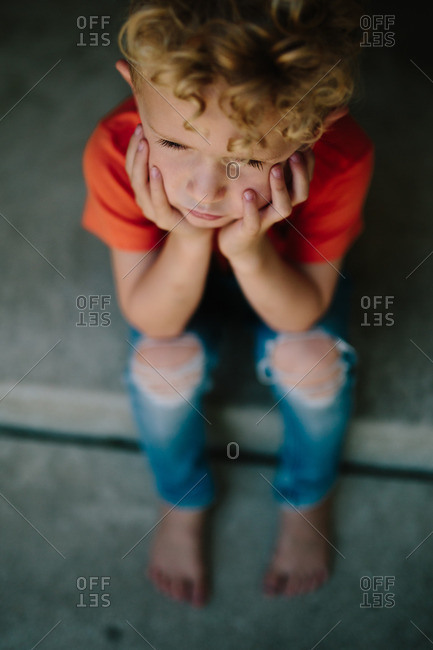 High angle of boy sitting on front porch