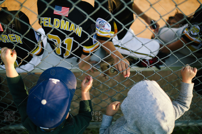 Two kids looking through metal fence at baseball players