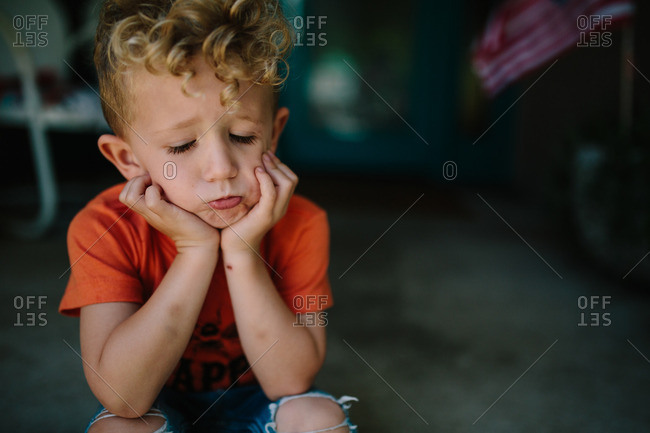 Boy sitting on front porch with chin resting on hands
